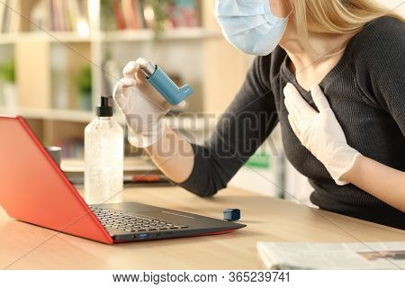 Asthmatic Woman Holding Inhaler Suffocating With Coronavirus Symptoms Sitting On A Desk At Home