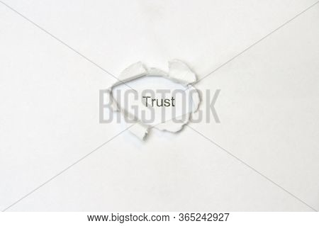 Word Trust On White Isolated Background, The Inscription Through The Wound Hole In The Paper. Stock