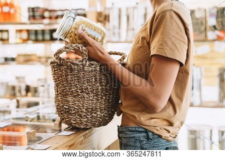 Woman Buying Products In Plastic Free Grocery Store. Glass Jar With Pasta In Hands Of Person In Zero