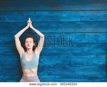 Woman Practicing Yoga On Background Of Blue Wooden Wall.