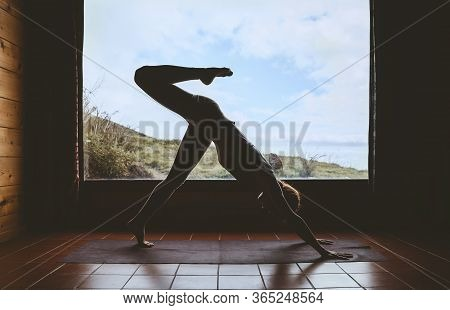 Silhouette Of Young Woman Practicing Yoga Indoors