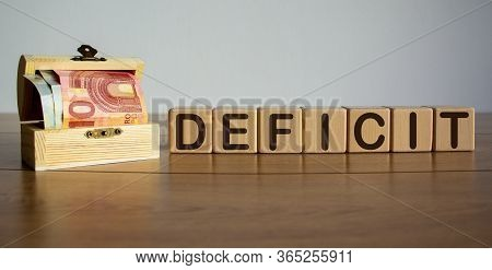 Concept Word Deficit On Cubes On A Beautiful Wooden Table, Small Chest With Euro Bills.