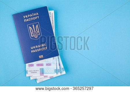 Ukrainian Passport And Banknotes On A Blue Background. The Concept Of Accumulation On Vacation And T