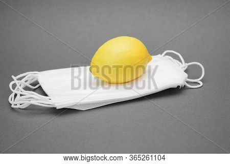A Yellow Lemon Is Located On A Pile Of Medical Masks. The Concept Of Strengthening The Immune System