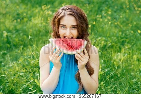 Pretty Young Woman Bites Piece Of Watermelon On Grass Background. Beautiful Girl Is Biting Slice Of