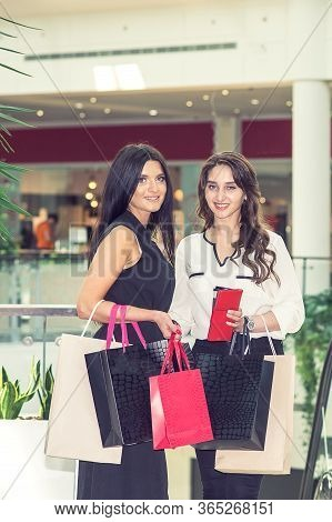 Two Smiling Young Women Are Looking At Camera At The Shopping Mall. Two Adult Girls With Paper Bags