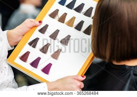 Women Hands With A Dye Color Catalog. Women Hair Color. Woman Choosing Hair Color In Dye Catalog. Cl
