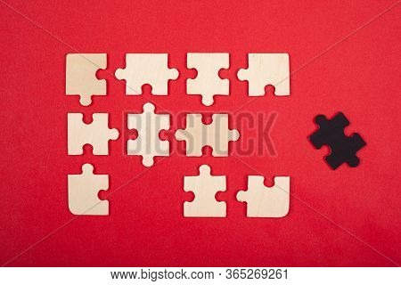 Puzzles White And Black Color On A Red Background. Close-up Top View. Leadership Guide Do Not Fit In
