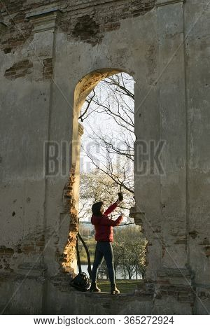 The Girl Climbed Into The Ruins Of A Tourist Attraction And Tries To Take A Selfie On The Phone.