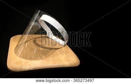 Medical Visor Lying On A Wooden Countertop On Black Background. Plastic Full Face Cover Visor. Prote