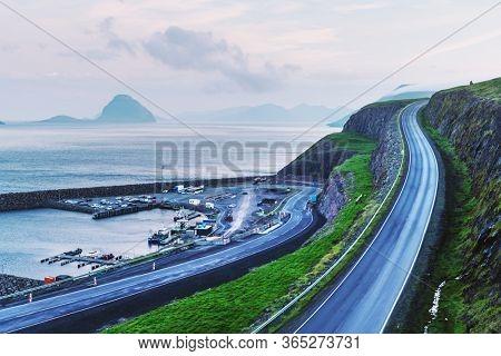 Foggy morning view of a pier with cars and boats near the Velbastadur village on Streymoy island, Faroe islands, Denmark. Landscape photography
