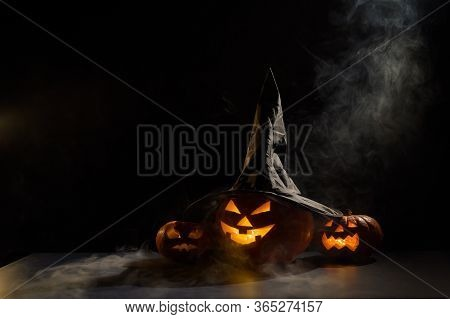 Spooky Orange Pumpkins For Halloween Stand In A Row On A Dark Background. Jack O Lantern In A Witch
