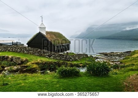 Summer view of traditional turf-top church in faroese village. Beauty landscape with foggy fjord and high mountains. Streymoy island, Faroe Islands, Denmark.