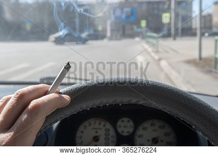 A Smoking Cigarette In The Hand Of A Smoking Car Driver While Driving Through The City Against The B