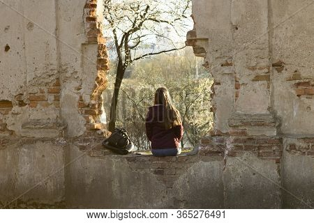 The Girl Sits With Her Back To The Viewer On The Ruins Of An Ancient Medieval Castle