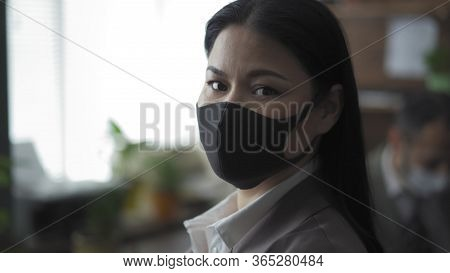 Well-dressed Businesswoman In Black Protective Mask Looks Back At Camera, Asian Young Woman Working