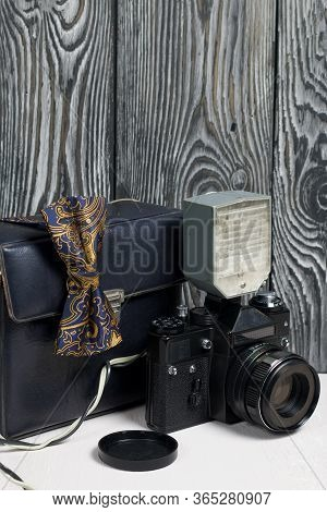 Photographer Accessories. Camera And Flash. There Is A Bow Tie On The Camera. Against The Background