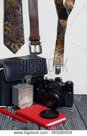 Photographer Accessories. Camera And Flash. Near Tie, Belt, Suspenders, Notebook And Pen. On Brushed