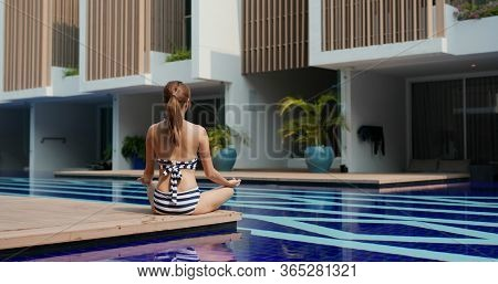 Woman do yoga at swimming pool