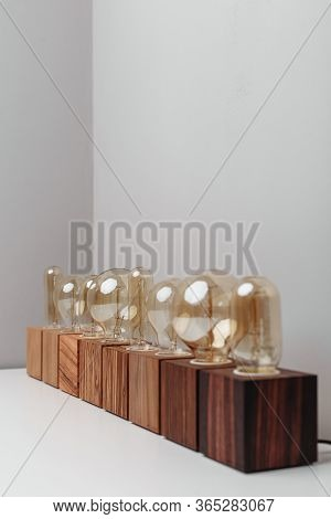 A Top View On A Row Of A Different Steampunk Style Old-fashioned Lamps With A Wooden Base. Mix Of An