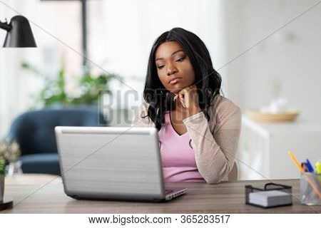 remote job, technology and people concept - african american bored or tired young woman with laptop computer working at home office