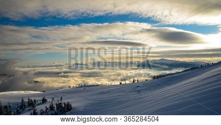 Aerial View Above The Clouds At Mountain Peaks Covered With Snow, Lighting By The Sun