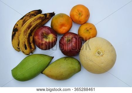 Upawas Fruits Variety Of Indian Muskmelon, Oranges, Mango, Banana And Apple. Heap Of Fruits From Ind