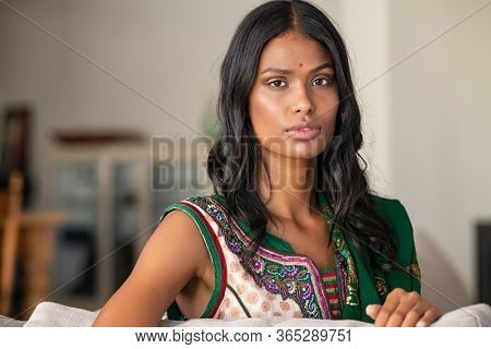Portrait of young indian woman in traditional saree clothing sitting on couch and looking at camera. Beautiful girl in sari with a bindi on forehead. Young hindu wife in traditional indian choli.
