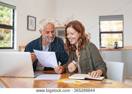 Mature smiling couple sitting and managing expenses at home. Happy senior man and mid woman paying bills and managing budget. Middle aged couple checking accountancy and bills while looking receipt.