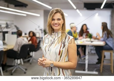 Portrait of beautiful business woman looking at camera while business team working in background. Executive woman standing in office. Happy and smiling creative businesswoman with co-workers.
