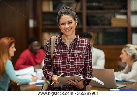 Happy university student looking at camera while her classmates studying in background. Portrait of smiling young woman holding notes and pencil with bag, standing in college library.