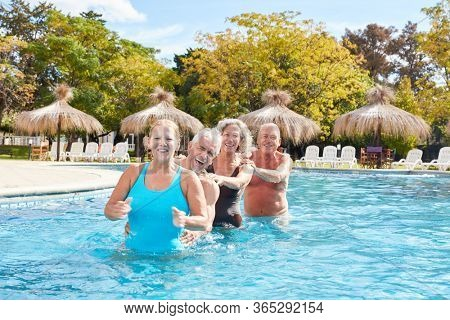 Cheerful seniors group has fun together in the pool of the wellness hotel