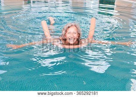 Vital senior woman in pool with swimming aid in rehab doing aqua aerobics