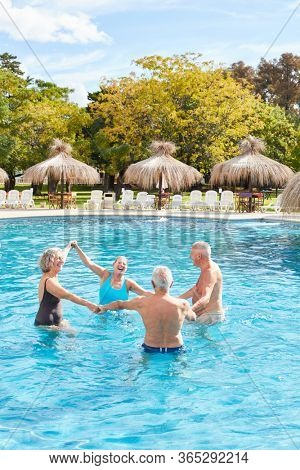 Senior group forms a circle in the pool at the aqua fitness in the spa hotel