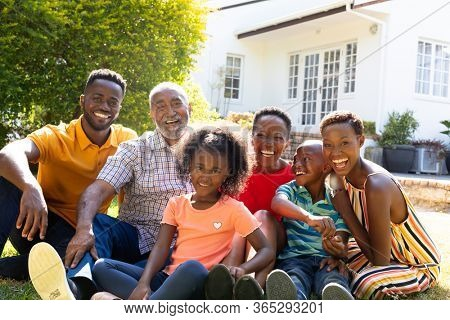Three generation African American family spending time in their garden on a sunny day, smiling and looking straight into a camera.