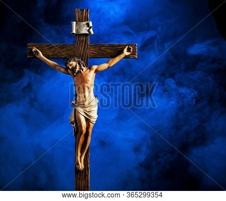 A Small Statue Of Jesus Christ On The Cross Against A Smoky Background