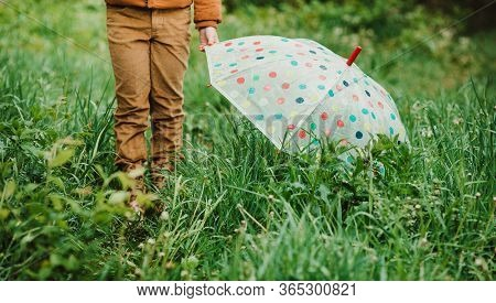 Feet Of Child In Yellow Rubber Boots And Colorful Umbrella In The Rain. Soft Focus