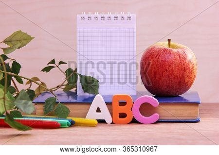 Abc Letters Near The Book And Colored Pencils. A Ripe Apple On The Book And A Houseplant Next To The