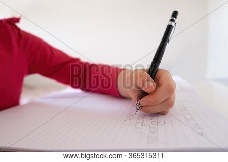 Caucasian Child Hand Writing With Mechanical Pencil In Notebook With Shallow Focus