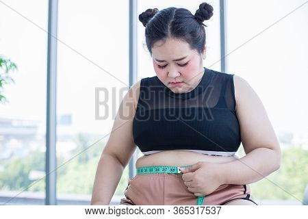 Asian Overweight Woman Measuring Fat Layer With Waistline At Home