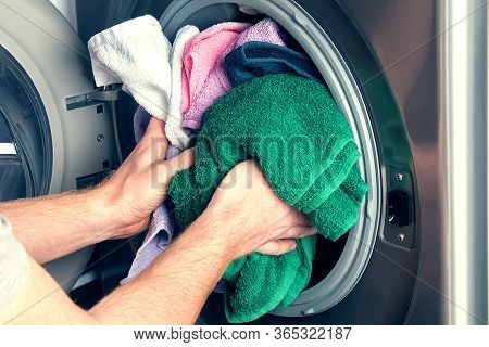 Man Taking Color Clothes From Washing Machine. A Drum Of Washing Machine Full Of Dirty Laundry In Ba