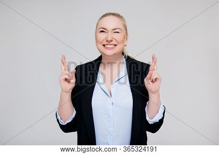 Expectation And Success - Portrait Of Hopeful Beautiful Woman Crossing Her Fingers Over Gray Backgro