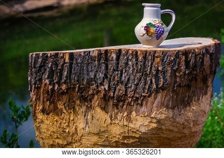 A Colorful Clay Jug Was Standing On A Small Tree Stump On A Sunny Spring Day