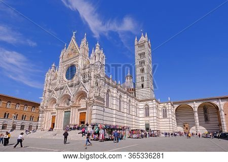 Siena, Tuscany, Italy, March 31, 2019: Tourists In Front Of The Dome Duomo Di Siena, Blue Bright Sky