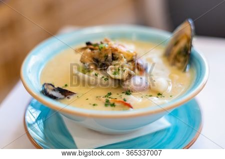 Seafood Soup Close-up. East Asian Cuisine. A Plate Of Seafood Soup. A Man With A Spoon Stirs Squid O