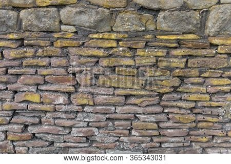 A Close Up View Of A Stone Wall With Moss And Grouting Around It
