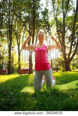 Young Athletic Girl Doing Fitness Exercises In A Summer Green Park, Training Day For Taking Care Of