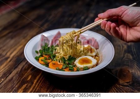 Eating Japanese Ramen With Chopsticks. On A Wooden Table. Japanese Ramen. Wooden Background. Traditi
