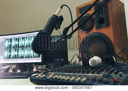 Radio Microphone, Mixing Console And Headphones On The Background Of The Monitor
