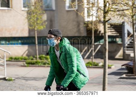 Ukraine, Kyiv - April 25, 2020: Boy Rides A Bmx On A Street Wearing A Medical Mask To Prevent Of Bac